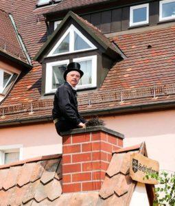 Schornsteinfeger auf einem Dach