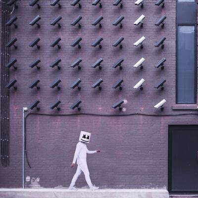 Person bewegt sich unterhalb vieler Überwachungskameras inkognito mit abgedecktem Gesicht