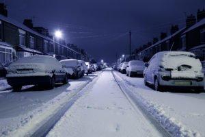 Parkende Autos am Rande einer verschneiten Straße im Winter