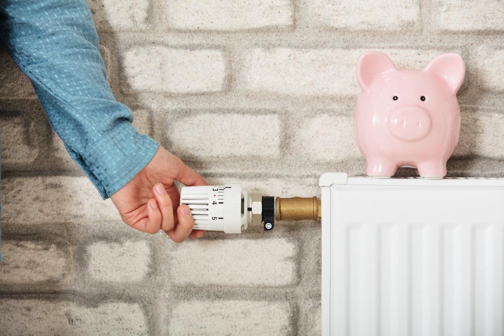 Eine Hand dreht das Thermostat eines Heizkörpers. Auf dem Heizkörper sitzt ein Sparschwein.