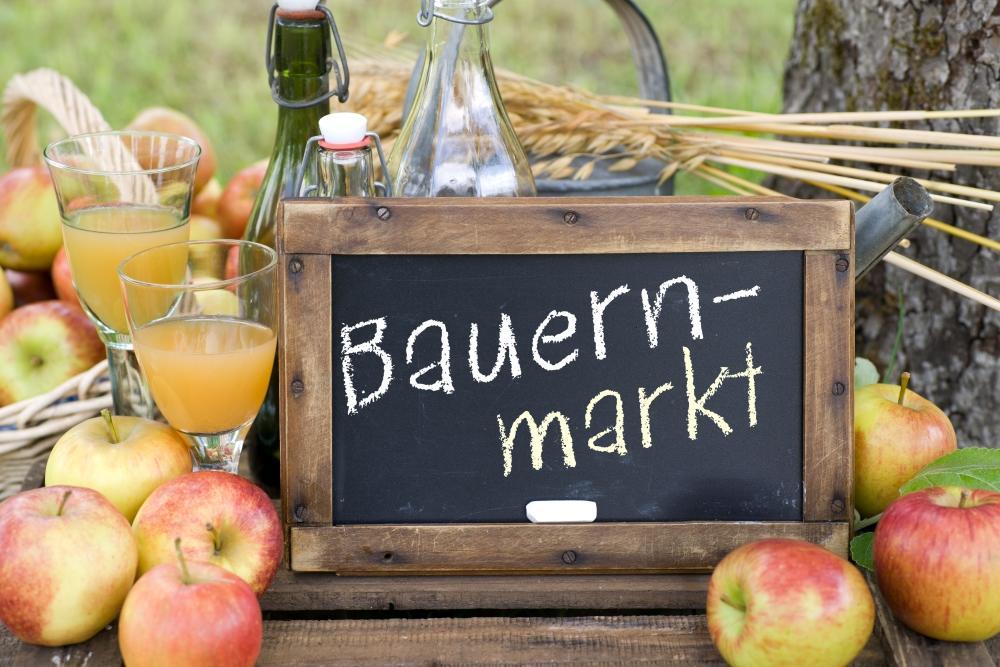 """Schild mit """"Bauernmarkt"""" und Äpfeln"""