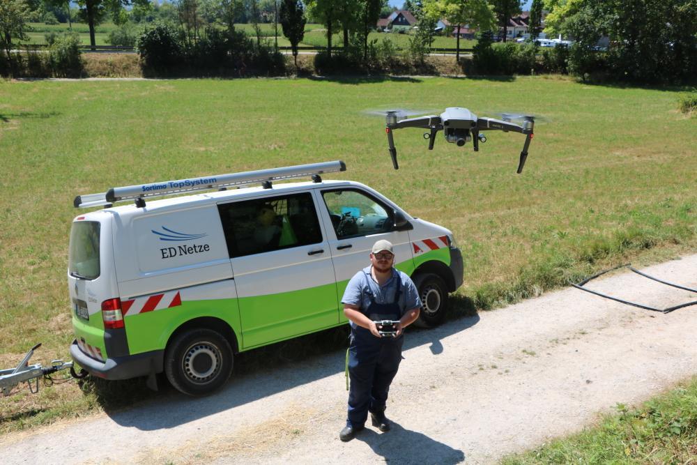 Betriebselektriker der ED Netze fliegt mit Drohne vor Fahrzeug der ED Netze.