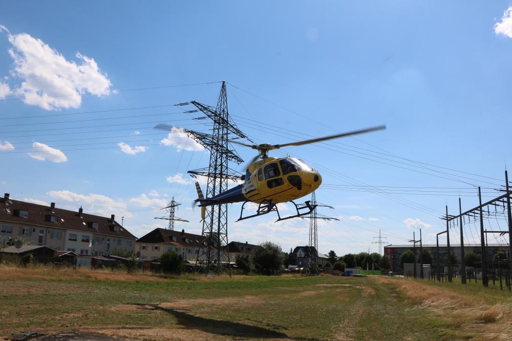 Hubschrauber landet vor Strommast