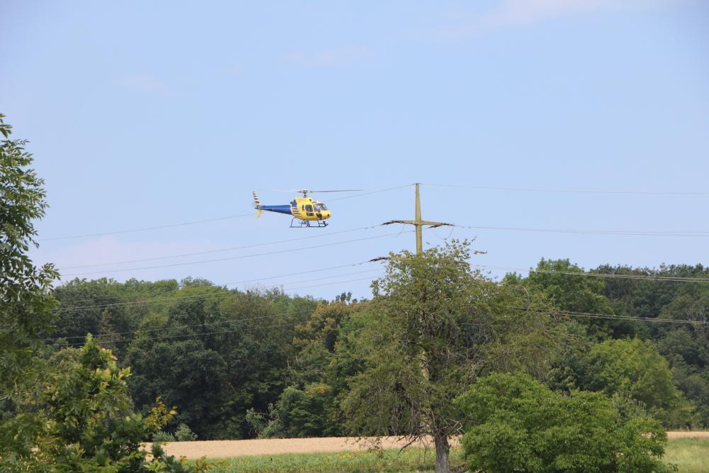Hubschrauber fliegt bei Leitungskontrolle nah an der Stromleitung entlang