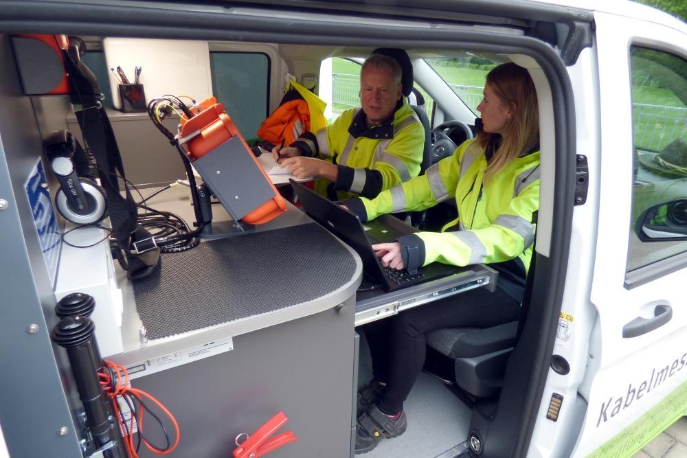 Zwei Mitarbeiter von ED Netze sitzen im Kabelmesswagen und werten Messergebnisse an Bildschirmen aus.