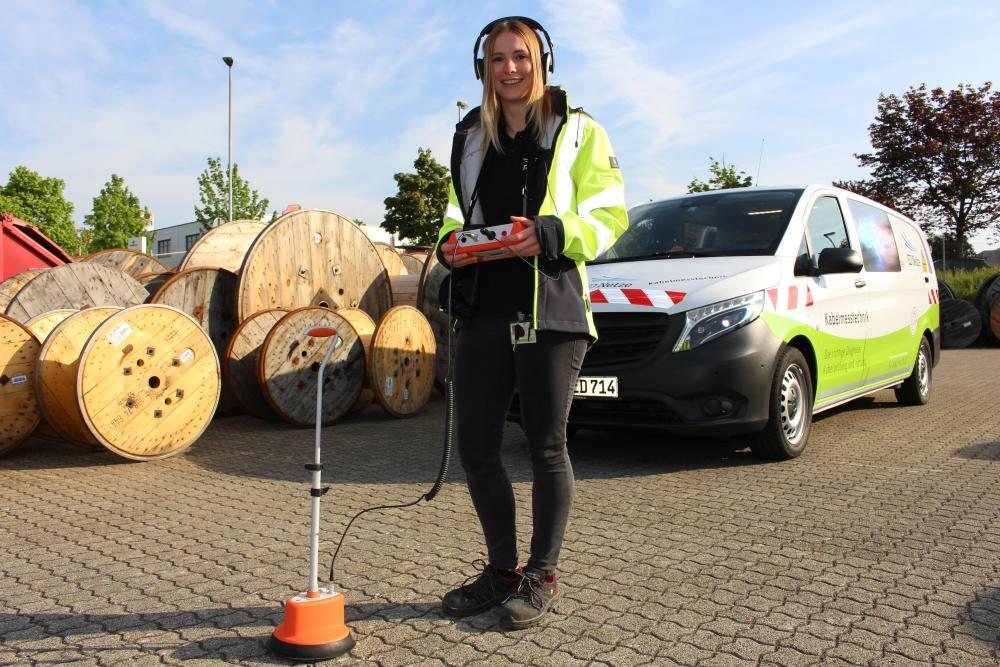 Eine Mitarbeiterin der ED Netze steht mit einem Messgerät vor dem Kabelmesswagen.