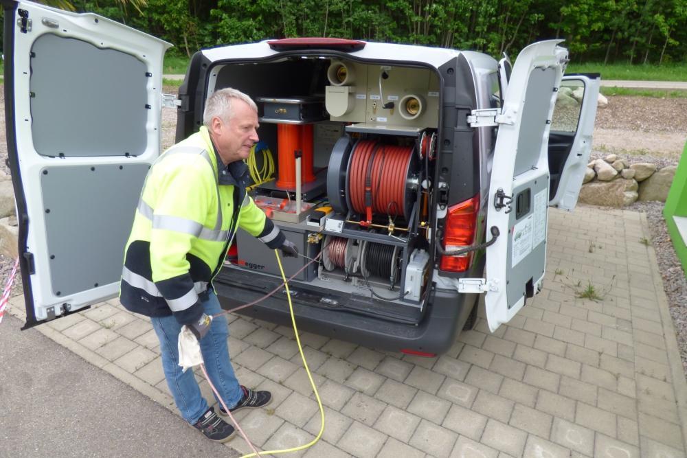 Ein Mitarbeiter steht vor dem Heck des Kabelmesswagens und rollt ein Kabel auf eine Kabeltrommel auf.