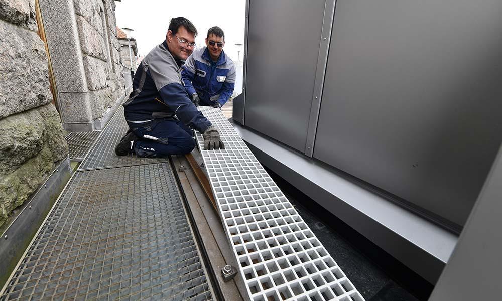 Mechaniker setzen Gitterrost bei Stauwehr ein