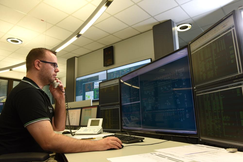 Mitarbeiter sitzt in der Netzleitstelle mit einem Telefon in der Hand vor vielen Bildschirmen.