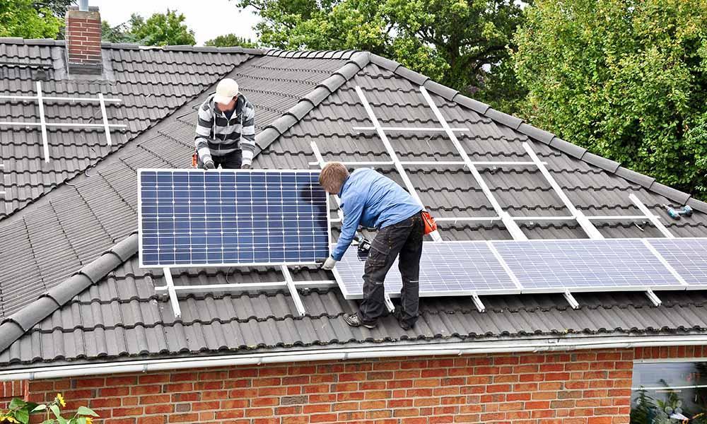 Techniker montieren auf ein Dach eine Photovoltaikanlage.