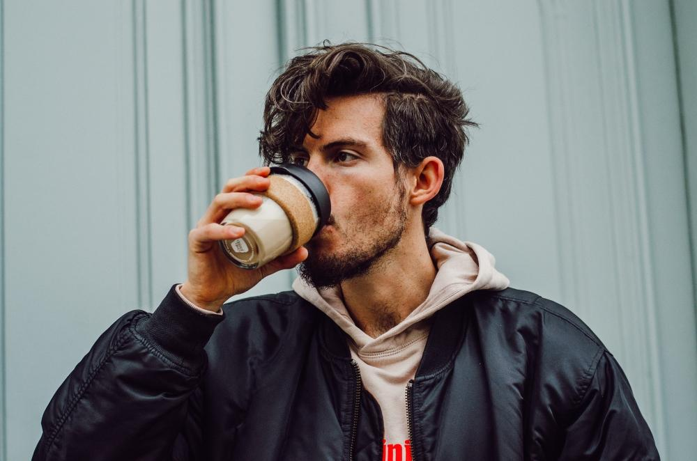 Mann mit Glas-Kaffeebecher in der Hand