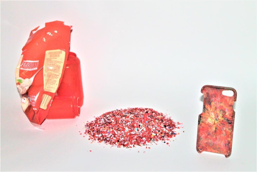 Plastikverpackung, Grablichter, Plastikranulat und eine Handyhülle aus Plastik gruppiert vor grauem Grund