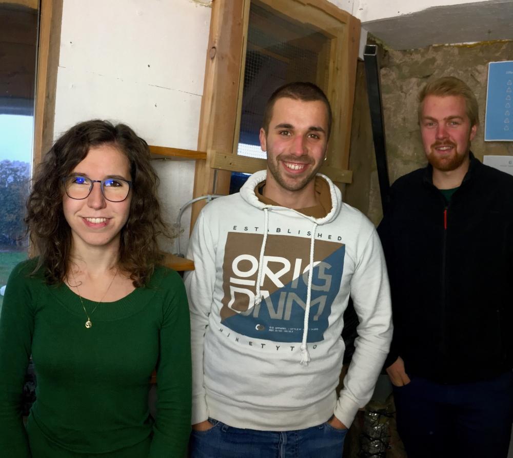Eine junge Frau und zwei Junge Männer lächeln in die Kamera.