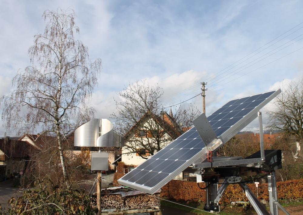 Ein Solarpanel und ein selbst gebautes Windrad stehen in der Sonne.