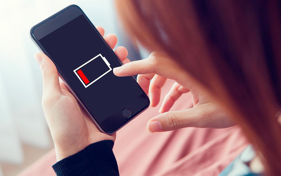 Frau sieht auf ihr Handy. Handy zeigt leeren Akku an.