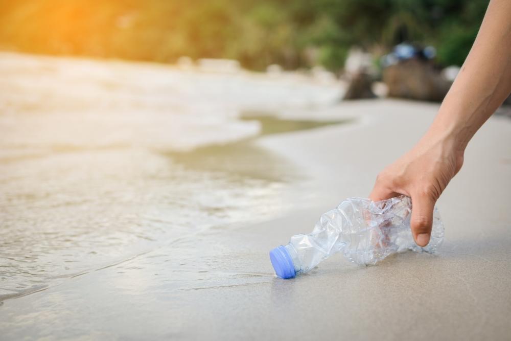 Hand hebt Plastikflasche, die am Strand im Sand liegt, auf..