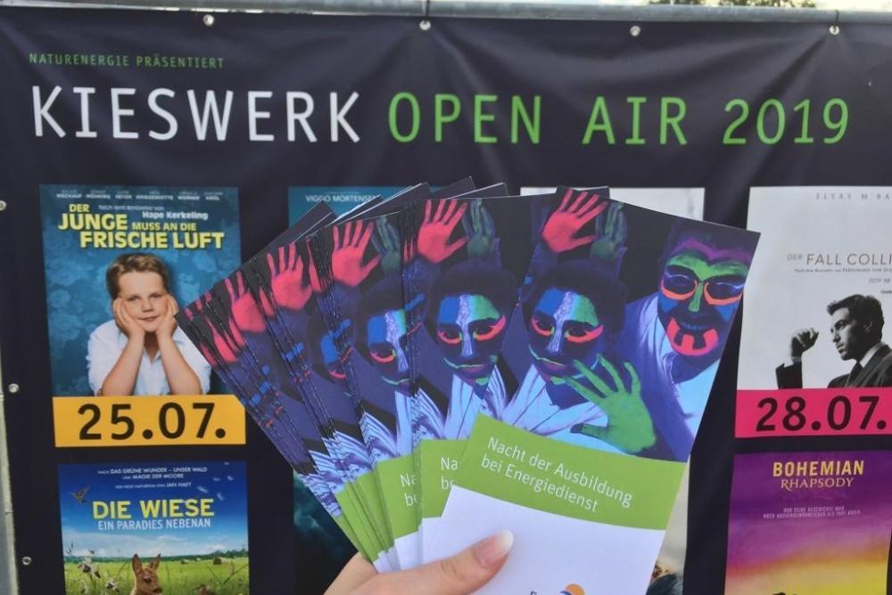 Azubine hält Flyer der Nacht der Ausbildung vor ein Plakat des Kieswerk Open Air