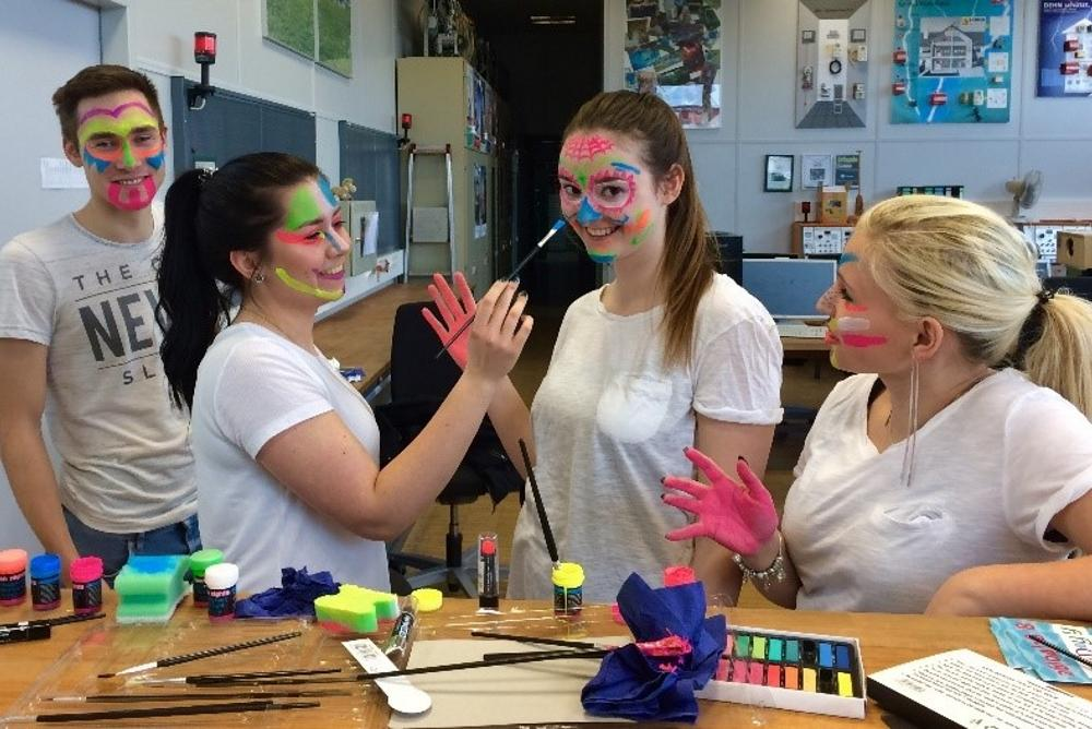 Auszubildende schminken sich mit Schwarzlichtfarben für die Nacht der Ausbildung