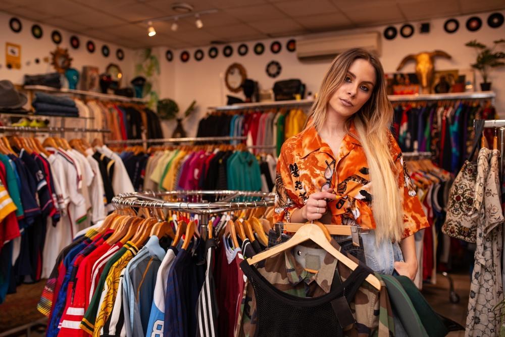 Frau steht in einem Kleidungsgeschäft an einen Kleiderständer gelehnt.