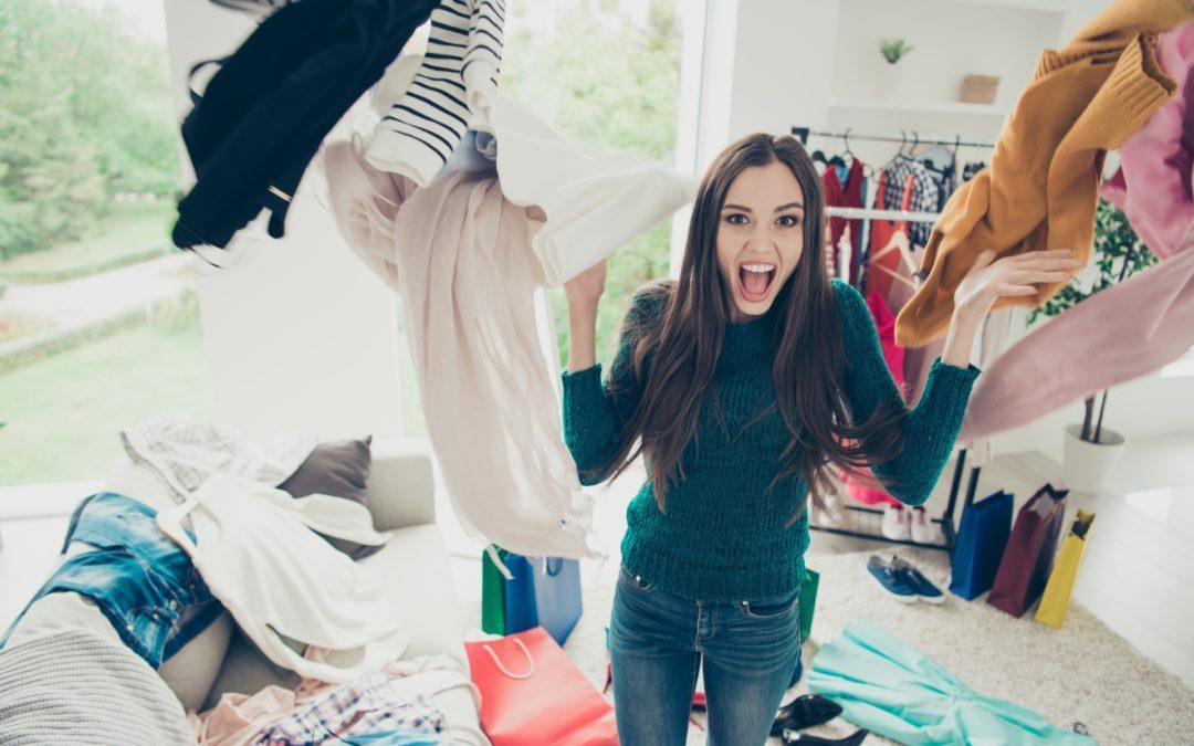 Frau schmeißt viele verschiedene Kleidungsstücke durch einen Raum.