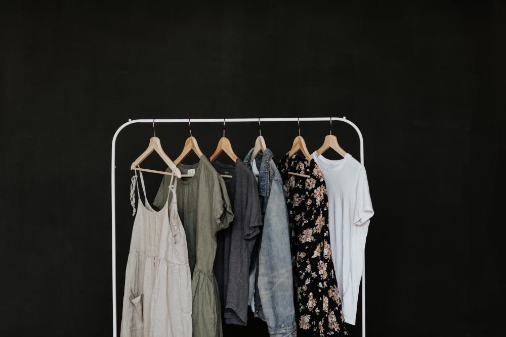 Verschiedene Kleider hängen auf Kleiderbügeln von einem Kleiderständer