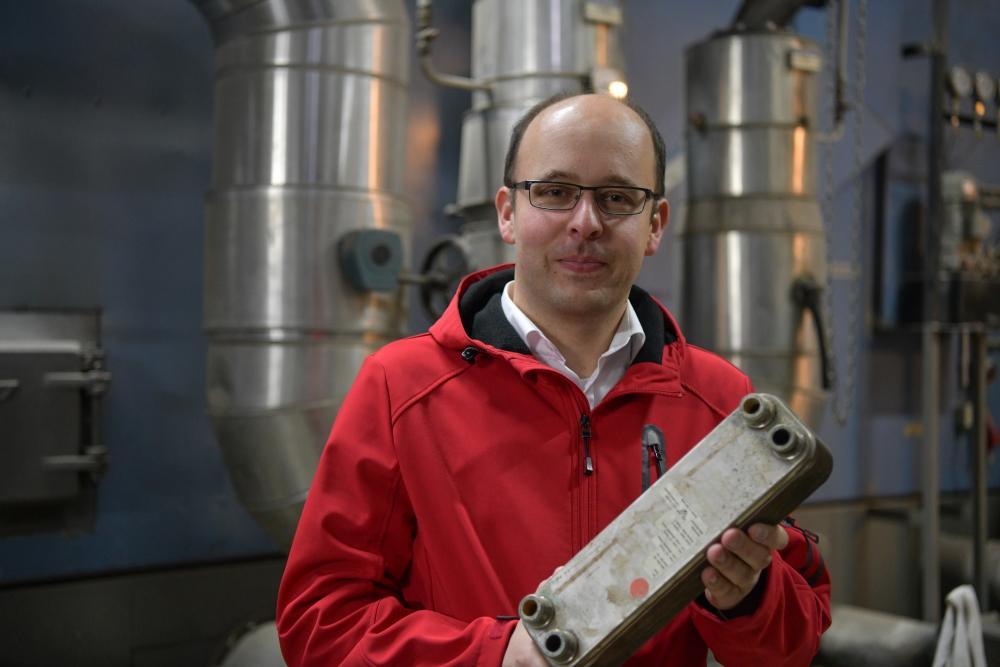 Martin Käfer steht im Heizwerk der Holzwärme Müllheim und hält einen Wärmetauscher in der Hand