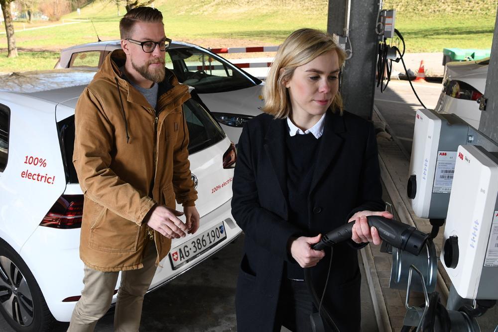 Frau und Mann laden Batterie eines Elektroautos an einer Ladestation