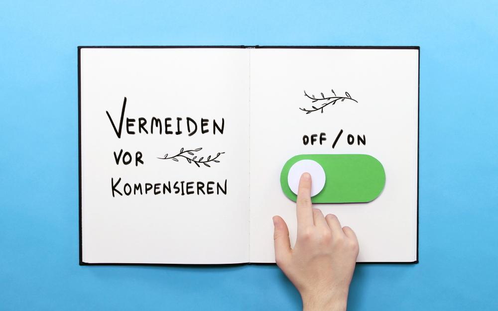 """Geöffnetes Buch. In dem Buch steht """"Vermeiden statt Kompensieren"""". Eine Hand zieht einen Schieberegler von """"on"""" auf """"off"""""""