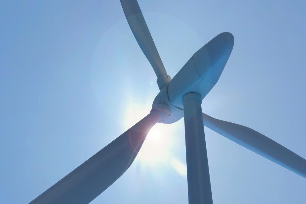 Windkraftanlage vor blauem Himmel in Sonnenschein
